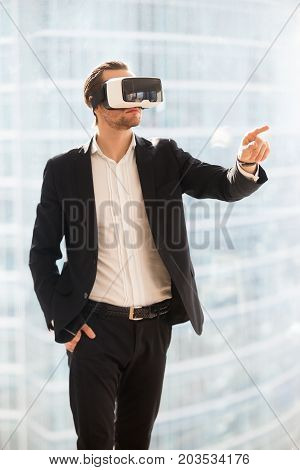 Businessman in VR glasses pointing finger in the air. Office worker or CEO immersed in virtual reality, innovative method of browsing web or managing business project through augmented reality.