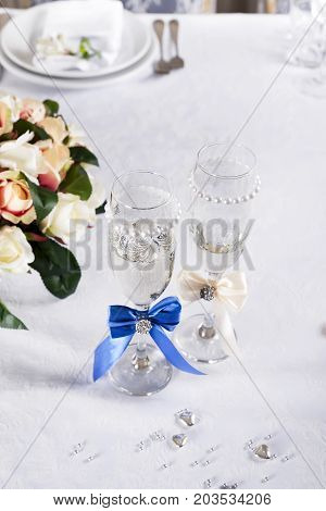 Two glasses of champagne on the background of the wedding bouquet copy space
