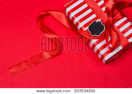 gift with red bow on red background. Free space for your text.