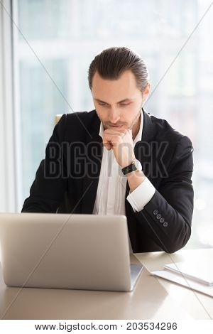 Serious thoughtful businessman working on laptop in office. Young entrepreneur taking care of business, browsing through important documents. Stock trader making investment decision, buying shares.