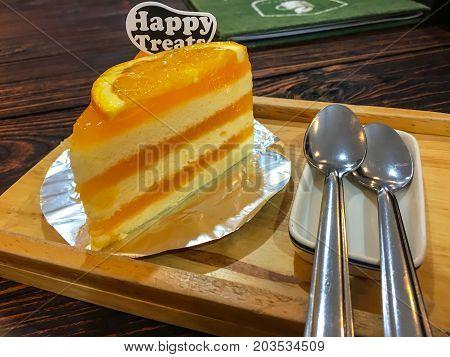 Orange cake on a wood table .
