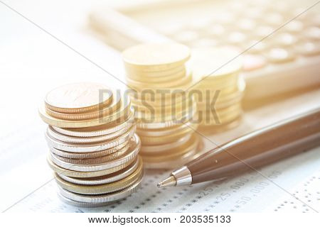 Business, finance, saving money, banking, loan, investment, taxes or accounting concept : Coins stack, calculator, pen and saving account book or financial statement on office desk table