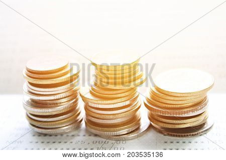 Business, finance, saving money, banking, loan, investment, taxes or accounting concept : Coins stack on saving account book or financial statement