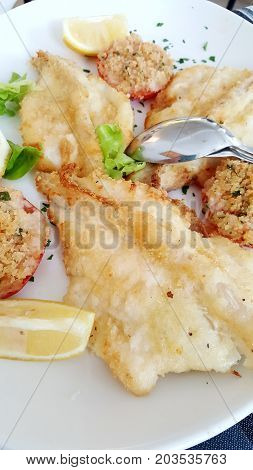 a dish with fried fish and tomatoes