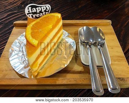 Orange cake on wood plate on a table