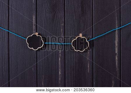 Clothespins with space for text on a black wooden fence