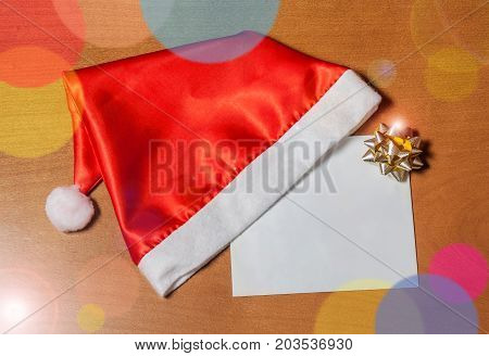 Greeting card with golden bow and Santa hat on wooden background