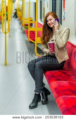 The girl speaks on a cell phone inside an empty subway train. Girl sits in a metro car with a smartphone