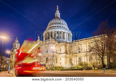 London England - The Saint Paul's Cathedral with famous old red double decker buses on the move at night
