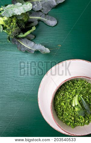 Broccoli Rice In Bowl On Green Background. Top View. Overhead. Copy Space. Shredded Broccoli.