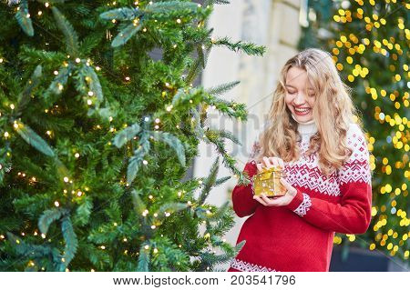 Young Woman On A Street Of Paris Decorated For Christmas