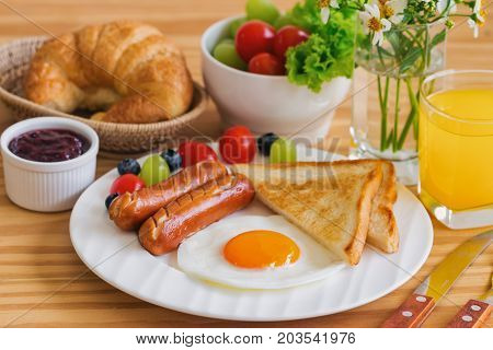 Homemade breakfast with sunny side up fried egg toast sausage fruits vegetable strawberry jam and orange juice in top view with copy space. Delicious homemade american breakfast concept for background. American breakfast served on table.