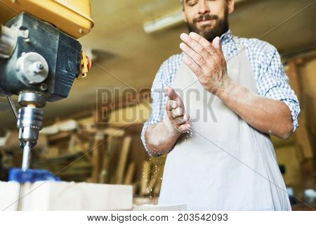 Low angle view of confident craftsman shaking sawdust from hands after completion of work with drill press machine, blurred background
