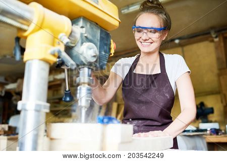 Attractive young woodworker with toothy smile using drill press machine in order to make holes in wooden plank, blurred background