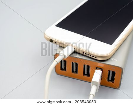 Close-up image of smart phone charging with multiport USB power adaptor on gray background with copy space Selective focus