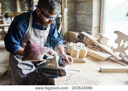 Profile view of talented craftsman restoring old wooden furniture with help of belt sander, interior of spacious workshop on background
