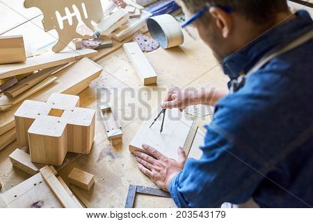 Over shoulder view of experienced carpenter using compass in order to draw circle on wooden plank, messy table covered with sawdust