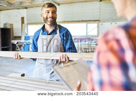 Cheerful middle-aged craftsman and his unrecognizable colleague making inventory at spacious warehouse