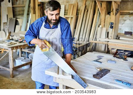 Concentrated bearded craftsman in apron cutting wooden board with hand saw while standing at table, interior of spacious workshop on background