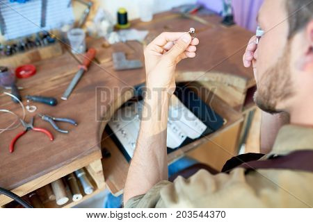 Portrait of jeweler looking at  ring through magnifying glass in workshop