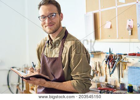 Portrait of smiling young man posing  in workshop studio of handmade crafts against background of table with tools, copy space