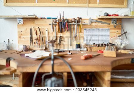 Background image of wooden workstation table in  workshop with tools for woodwork and metalwork on it