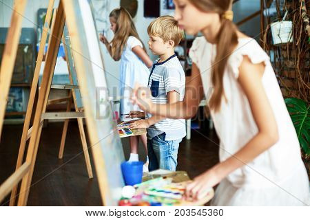 Talented children with wonderful imagination wrapped up in drawing while having class at art studio, they using gouache and watercolors