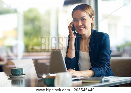 Smiling young white collar worker looking at camera while talking to her colleague on smartphone, interior of modern coffeehouse on background, view through panoramic window