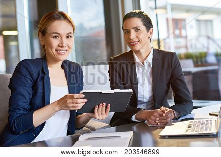 Group portrait of attractive white collar workers looking at camera with toothy smiles while having working meeting at cozy small coffeehouse with panoramic windows