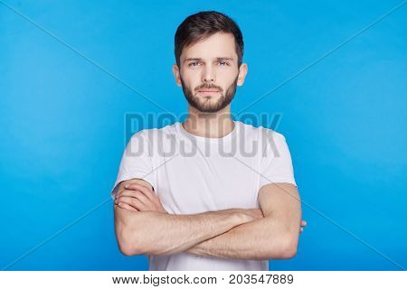 Studio shot of sceptic suspicious young Caucasian man standing at blue wall keeping arms crossed wearing stylish white shirt looking serious concentrated at camera with confident face expression.