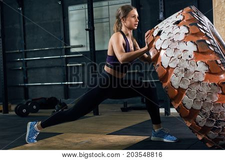 Side view portrait of strong young woman flipping heavy tire during cross workout in modern gym