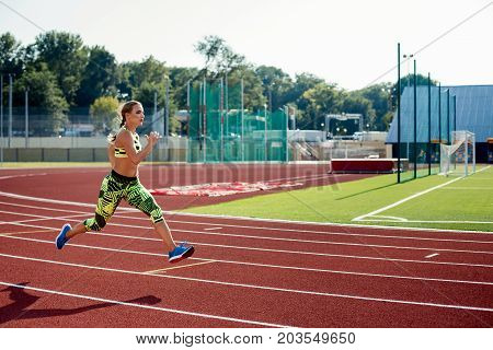 Beautiful young woman exercise jogging and running on athletic track on stadium. Red treadmill in sport field.