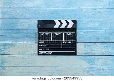 movie clapper on blue wood table ; film cinema and video photography concept retro style
