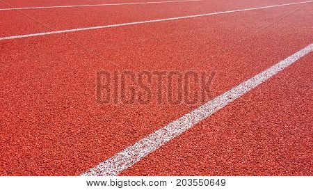 Sport Background. Running track in outdoor. Red Jogging rubberized athletic track with a white dividing lines at the stadium under the open sky