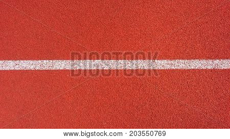 Sport Background. Decorative coating at the stadium in outdoor. White line in red sporting a rubberized Jogging track on the street stadium view from above