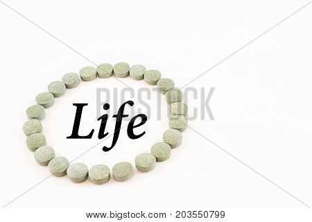 Circular outline formed by spirulina pills with word life inside. Supplement of vitamin B12. White background.
