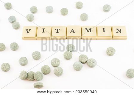 Vitamins written with chips and tablets of spirulina with B12 scattered. White background.