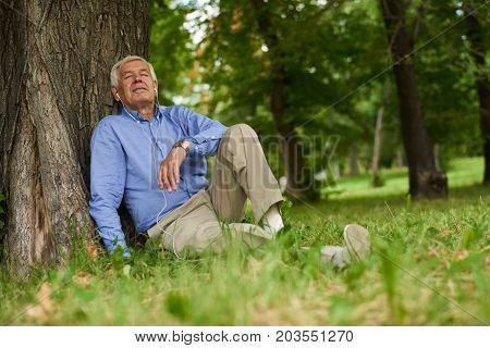 Portrait of modern senior man relaxing listening to music from smartphone  in park sitting on grass with eyes closed