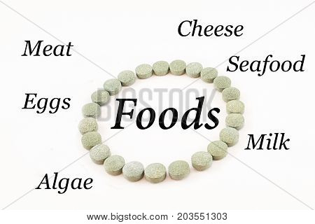 Contour of a circle made up of spirulina pills with word foods inside. Supplement of vitamin B12. White background.