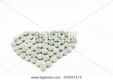 Heart made up of spirulina pills. White background.