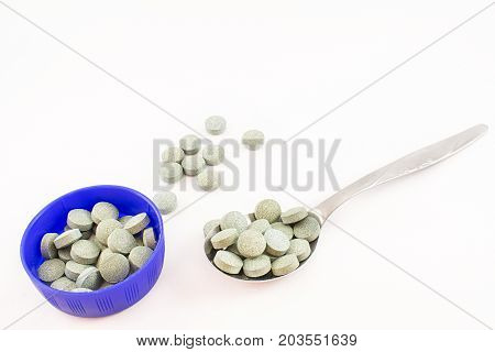 Aluminum spoon and container blue whit pills spirulina. White background.