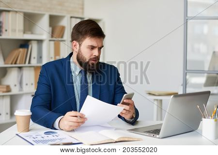 Portrait of bearded marketing expert working at desk in office, frowning looking at computer screen