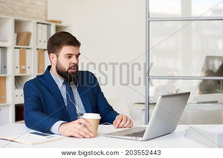 Portrait of young bearded businessman in conference call with partners