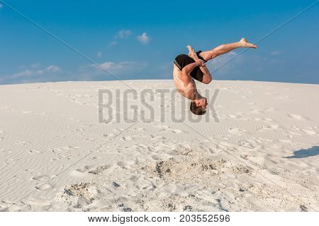 Portrait of young parkour man doing flip or somersault on the sand. Freezed moment of beginning doing bounce.