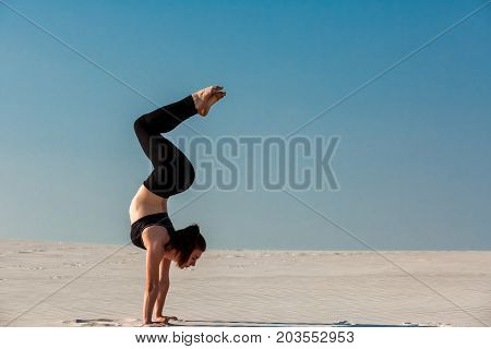 Young woman practicing inversion balancing yoga pose handstand on beach with white sand and bright blue sky