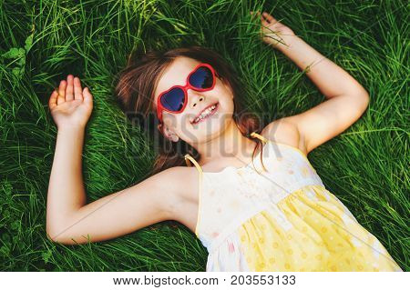 Outdoor portrait of pretty little girl wearing heart shaped sunglasses lying on fresh green grass. Party for children summer fun happy childhood. Top view