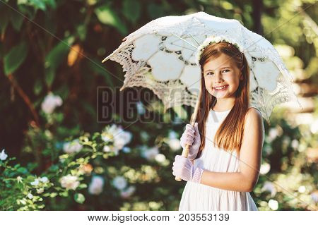 Outdoor portrait of romantic little girl wearing white dress gloves flower headband holding lace umbrella