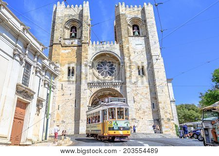 Lisbon, Portugal - August 25, 2017: historic Tram 28, most famous tram line, in front of Lisbon Cathedral in Alfama. Lisbon street with typical yellow tram and Se de Lisboa. Horizontal shot.