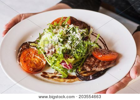 Medallions with grilled vegetables on plate bringing to customer. Meat, tomatoes, eggplant and green salad with grated cheese, serving in restaurant