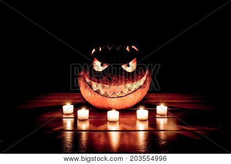 Spooky smiling halloween pumpkin in burning fire candles flames. The big helloween symbol has a mad face glowing eyes mouth and glow teeth on wooden table. Black orange nightmare of October 31st.